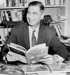 Dr Seuss seated at desk covered with his books, World Telegram and Sun photo by Al Ravenna